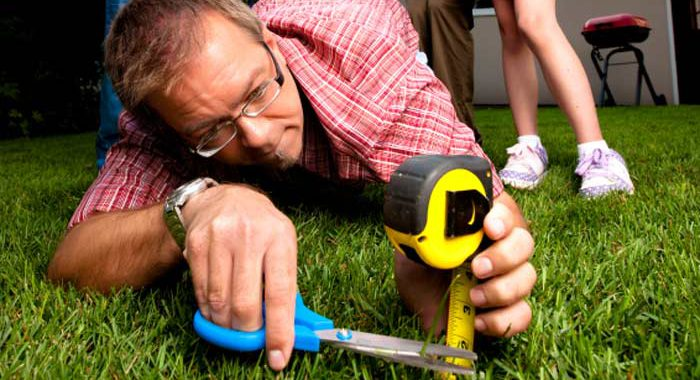 Man using measuring tape and scissors in grass to set the right mowing height