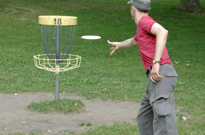 Man playing disc golf throwing frisbee at 18 hole