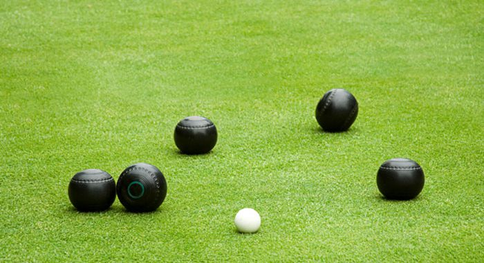 Lawn bowling game on lawn, 5 black bowling balls and small white ball