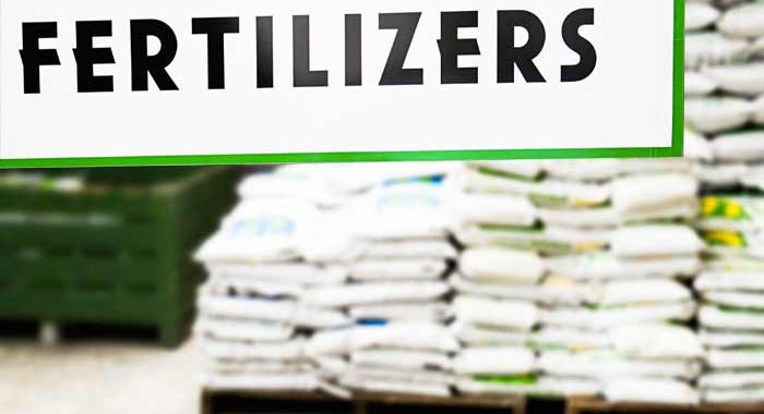Fertilizers sign with bags of fertilizer behind it