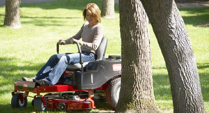 Woman on Toro Riding zero-turn Mower around trees