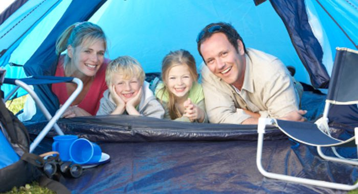 Family camping in backyard smiling inside tent
