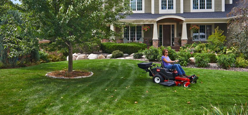 Woman sitting on Toro Timecutter Z Seed Spreader in front lawn