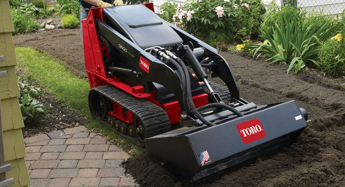 Worker using Toro Dingo to fix lawn grade problems