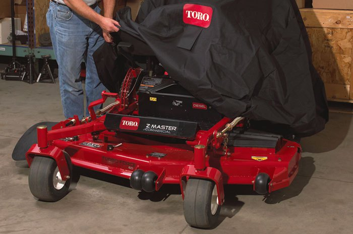 Man putting toro cover on Toro Z master commercial mower