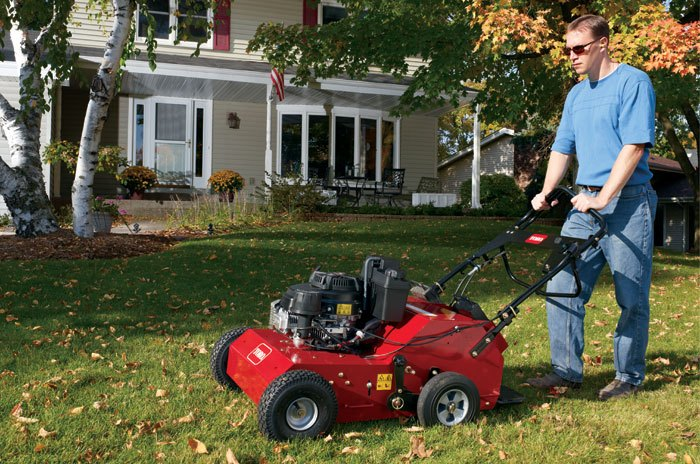 Man mowing lawn with Toro mower in Fall