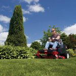 Man sitting on riding Toro Zero-Turn Mower on lawn