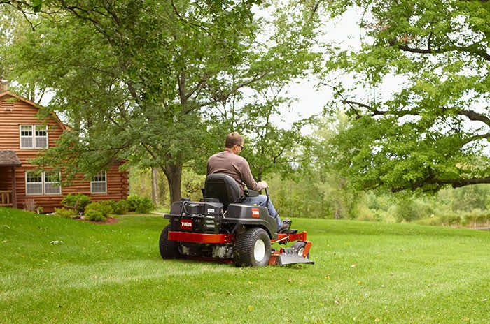 Man mowing with Toro riding lawn mower on property