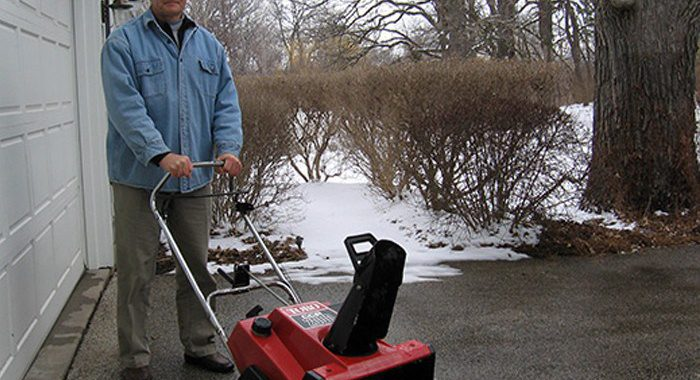 Man in blue jacket with Toro snowthrower on driveway