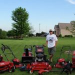Man standing next to 7 different Toro outdoor lawn equipment products