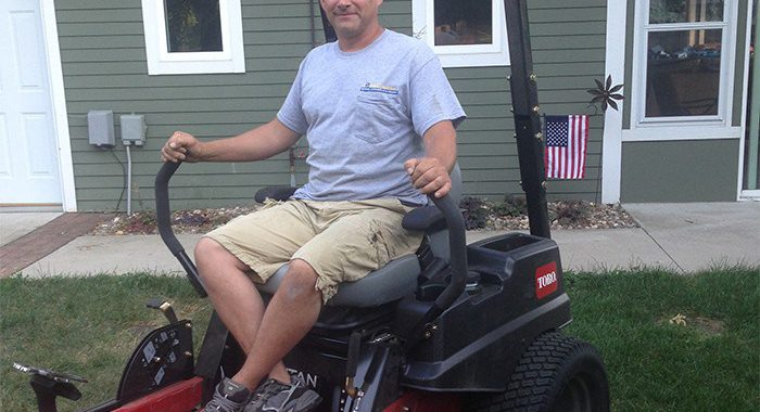 Man smiling on Toro riding lawn mower in front yard