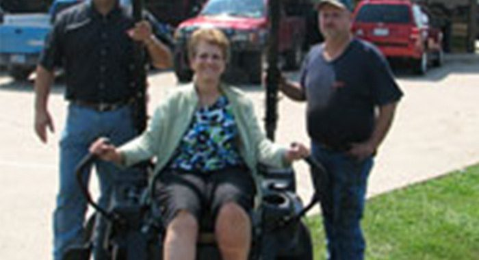 Woman sitting on riding lawn mower with two men standing on either side