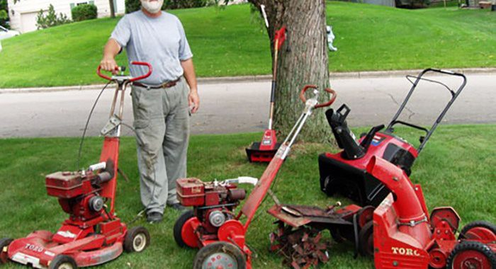 Man standing next to 5 different Toro outdoor equipment tools