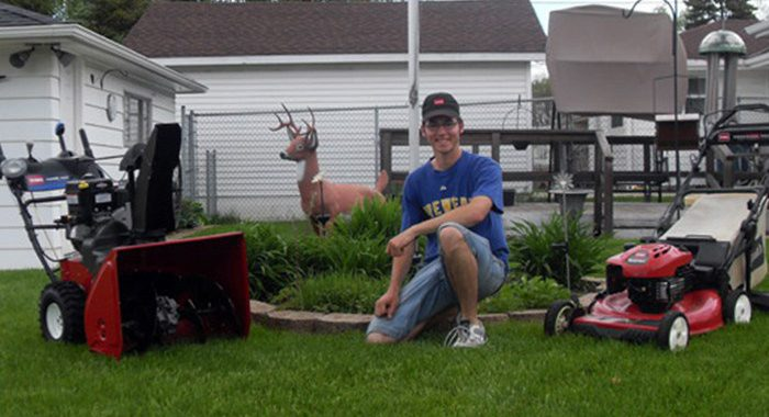 Man kneeling in between two Toro mowers smiling