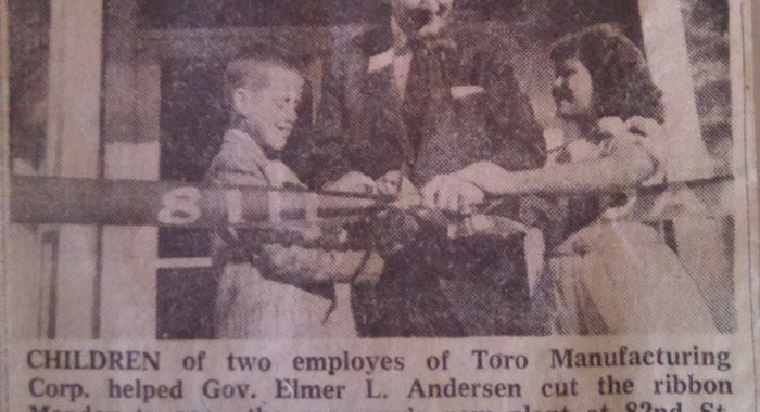 Newspaper clipping of Toro cutting ribbon to open company's new location in Bloomington