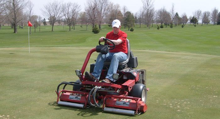 Man riding on Toro golf lawn mower on golf course