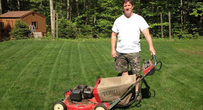 Man in tshirt showing off old school lawn mower in backyard