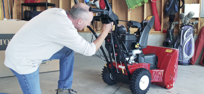 Man assembling a Toro Two-Stage Snowblower