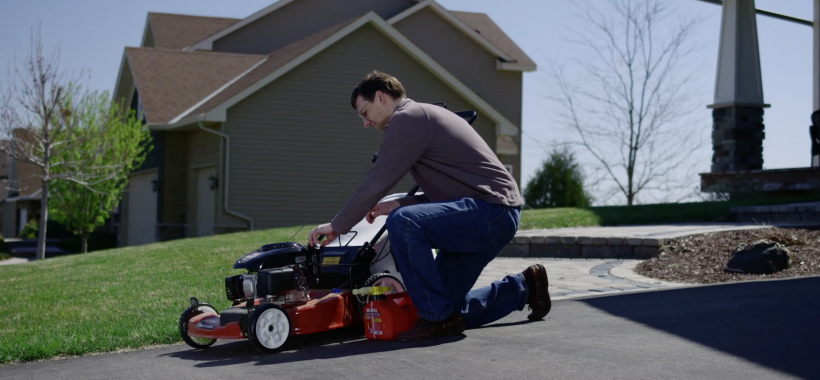 Man on driveway fixing lawn mower so it starts