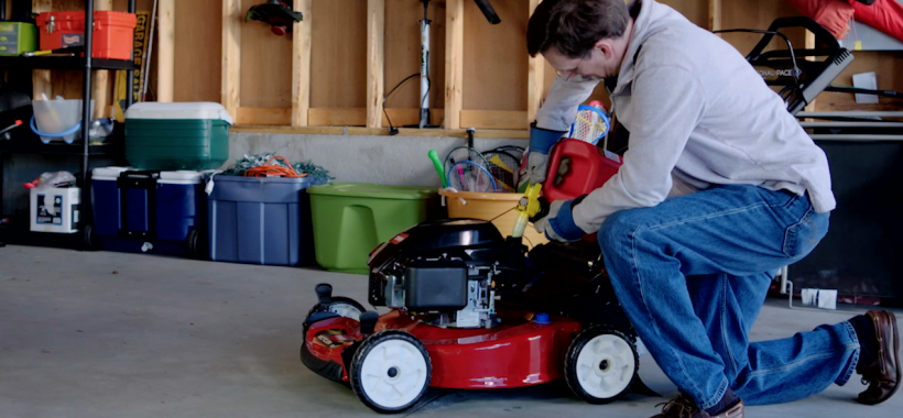 Man filling Toro lawn mower with gas in garage