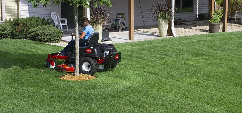 Woman mowing on toro riding lawn mower circling tree