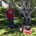 Man smiling next to big tree and toro push mower