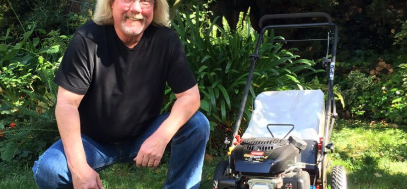 Man crouching next to Toro recycler 88 in yard