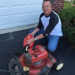 Man smiling fueling Toro push mower in driveway