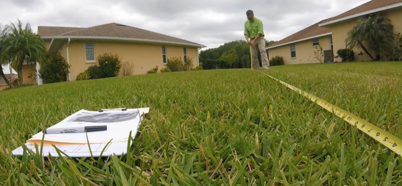 Man with measuring tape in the grass, measuring his lawn