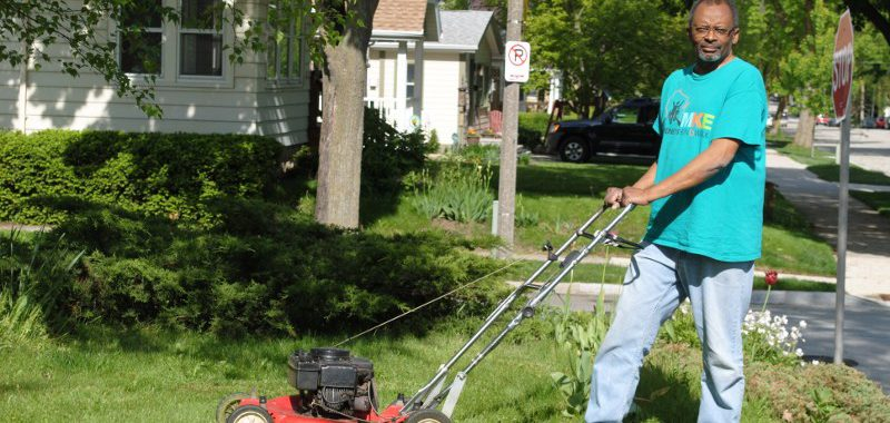 Man on the edge of yard near stop sign posing with Toro push lawn mower