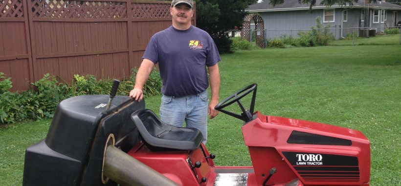 Man standing next to Toro Riding Lawn Tractor with brown fence behind him