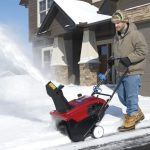 Man in coat and hat clearing snow from driveway with Toro snow blower