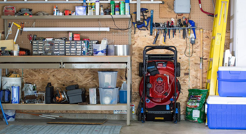 Garage filled with tools and outdoor equipment, Toro stow away mower leaning against wall