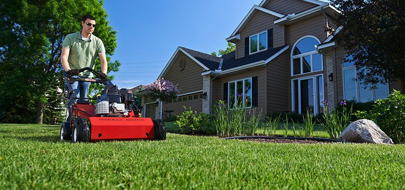 Man pushing Toro Hydraulic Aerator 23515 in front yard