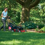 Woman mowing with Toro push lawn mower in the spring