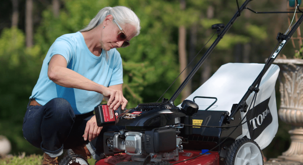 Woman pouring oil into Toro push lawn mower