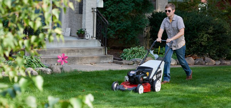 Man using Toro push lawn mower in backyard