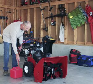 Man refilling gas in Toro snow blower to get ready for storage