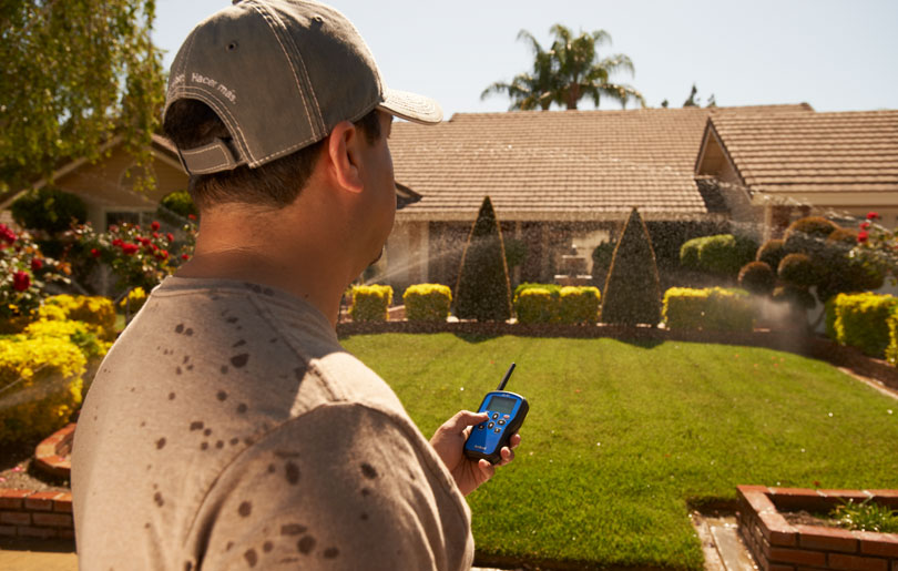 Man looking at lawn with Toro irrigation controller in hand