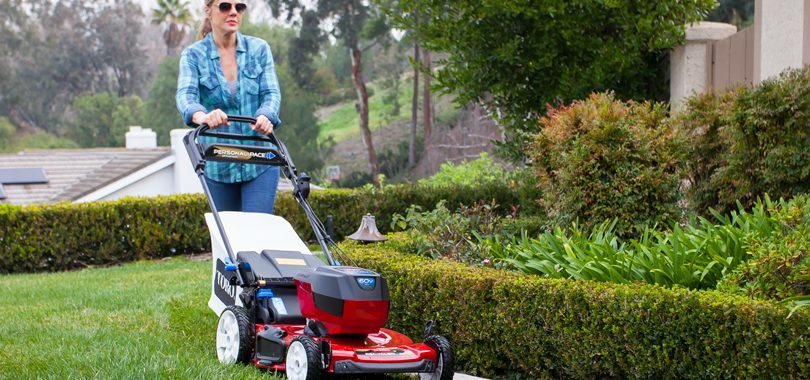 Woman using Toro 60V Personal Pace Push Lawn Mower