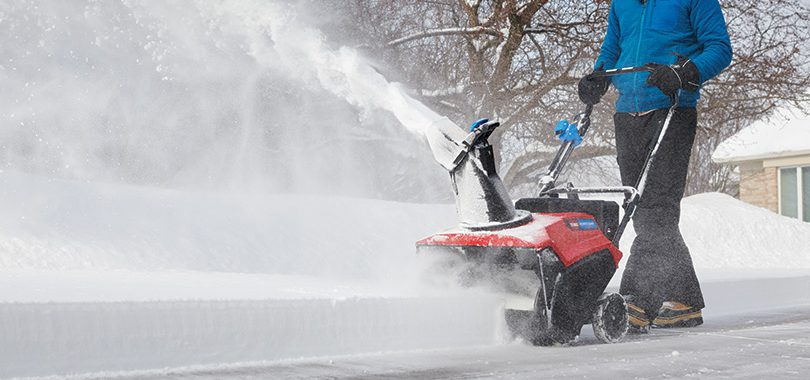 Man using Toro Power Clear snowblower on driveway